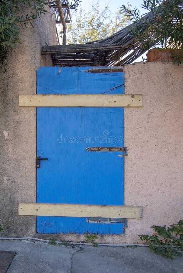 La vieille porte superficielle par les agents en bois a peint le bleu fermé avec les panneaux en bois photographie stock