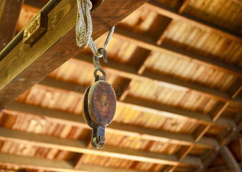 La vieille poulie en bois accrochant dans des constructeurs d'un bateau font des emplettes photo libre de droits