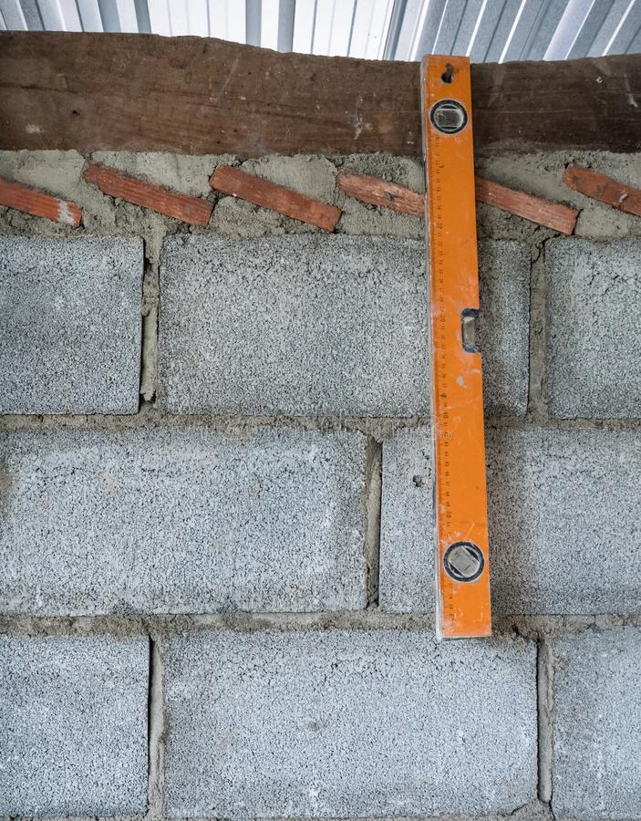 La vieille règle de niveau accroche sur le mur de briques photographie stock libre de droits