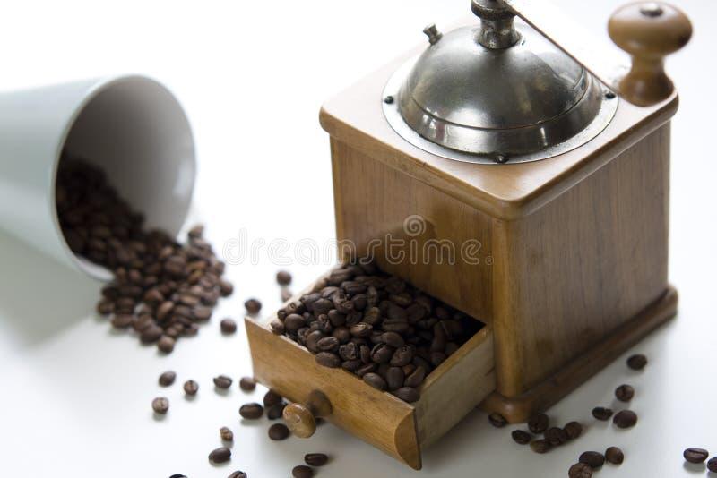 La vieille rectifieuse de café a rempli de graines de café entières photo stock