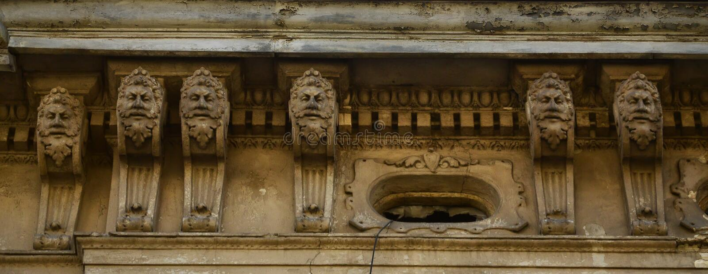 La vieille sculpture du XVIIIème siècle sous forme de têtes humaines, qui orne la façade des gratte-ciel à Lviv, Ukraine photographie stock