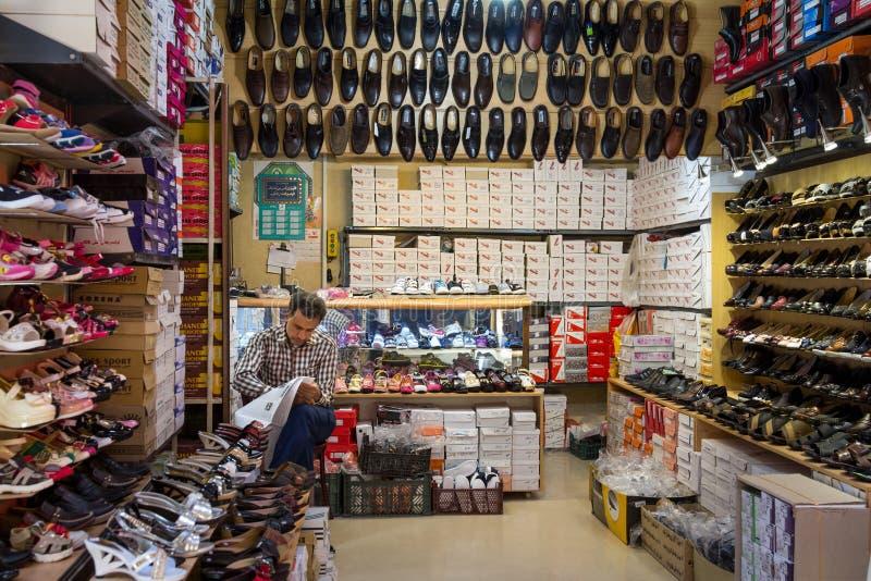 La vieille vente marchande iranienne chausse le journal de lecture dans le Farsi dans le bazar de Yazd Khan Yazd est l'une des vi image stock