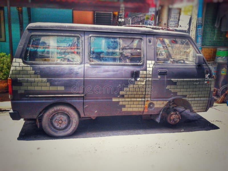 La vieille voiture grise a garé en raison de la fuite et de la lumière du soleil de pneu dans le dayligh images libres de droits