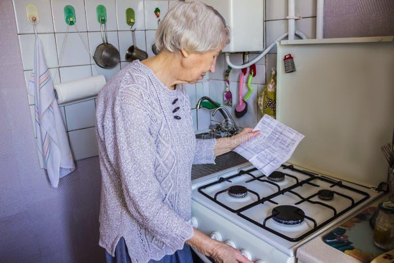 La vieja ama de casa mayor en casa y examina cuentas del gas y de la electricidad fotos de archivo libres de regalías