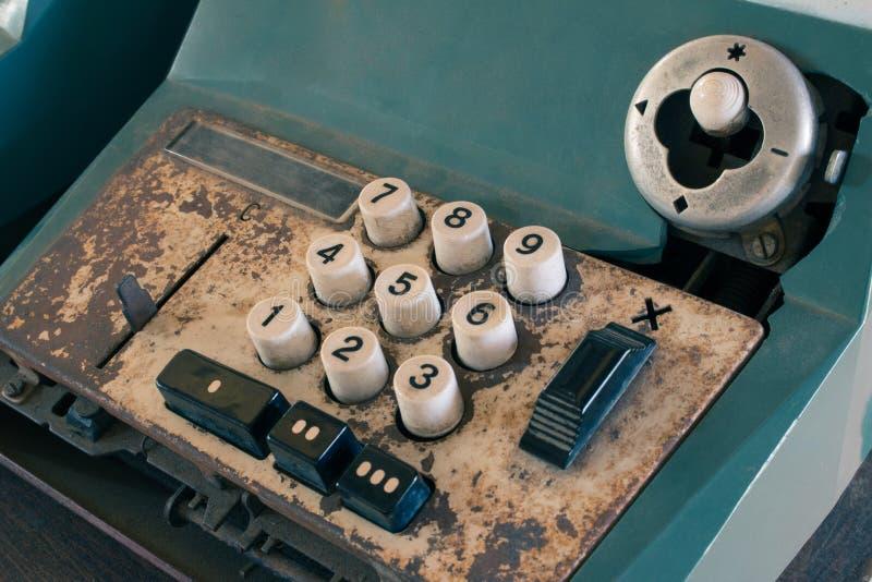 La vieja caja registradora antigua, las máquinas sumadoras o la antigüedad calculan en colmado viejo fotos de archivo