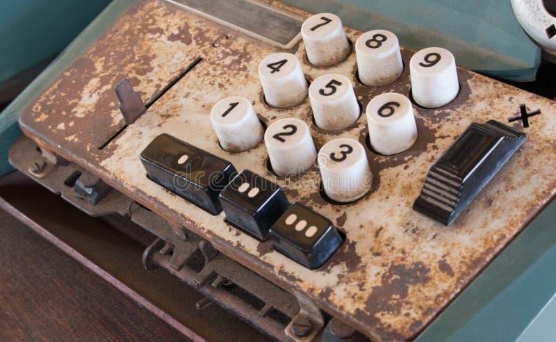La vieja caja registradora antigua, las máquinas sumadoras o la antigüedad calculan en colmado viejo imagen de archivo