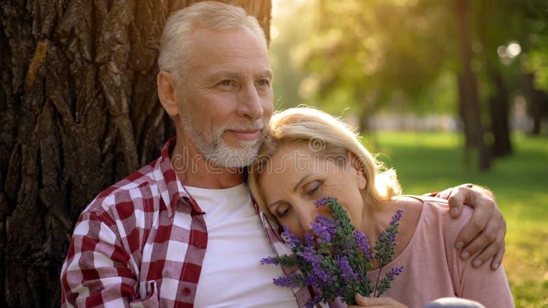 La vieja mentira femenina encendido sirve el hombro, par mayor que se sienta en parque cerca del árbol, fecha imagenes de archivo