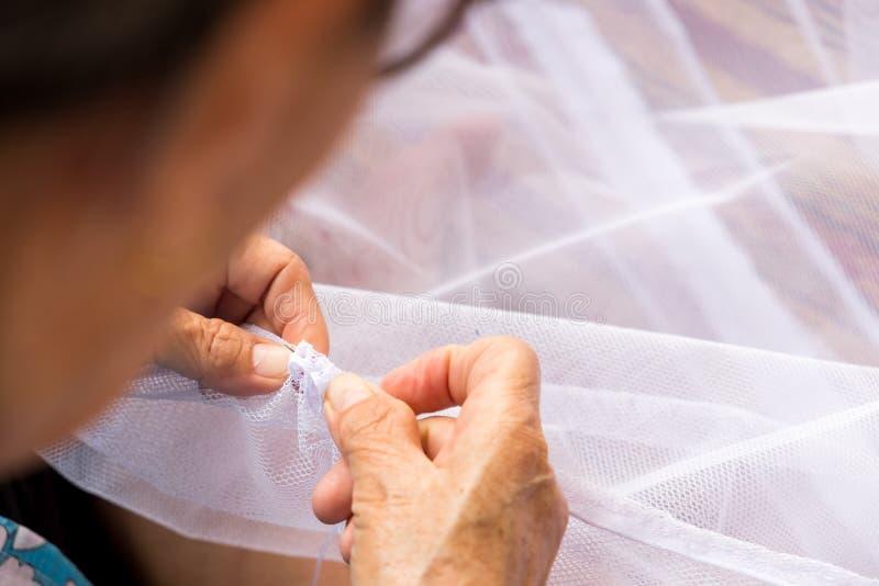 La vieja mujer de la alcantarilla está cosiendo la tela con la aguja para hacer la red para fotografía de archivo