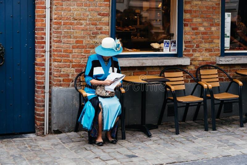 La vieja mujer refinada se vistió en la sentada azul en una terraza en la calle de Brujas imagenes de archivo
