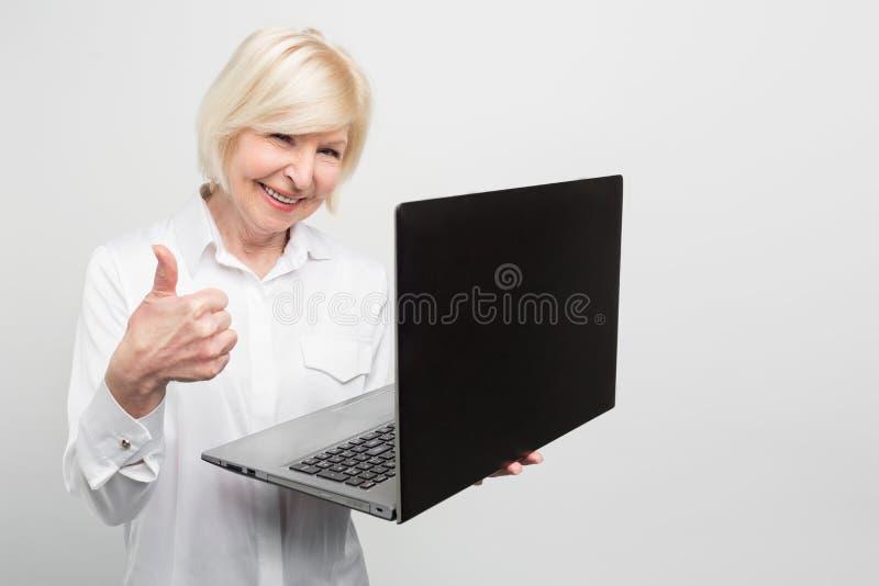 La vieja pero moderna mujer está sosteniendo un nuevo ordenador portátil Ella le gusta utilizarlo La señora prefiere conocer evet fotos de archivo libres de regalías