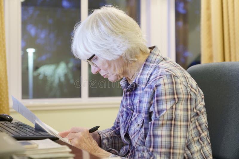 La vieja persona mayor mayor que aprende el ordenador y las habilidades en línea de Internet de la pensión y de las actividades b fotografía de archivo libre de regalías