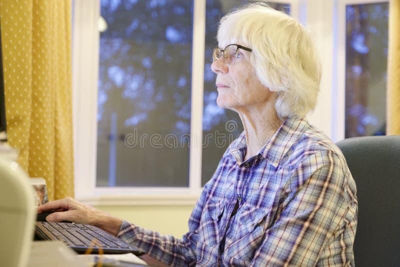 La vieja persona mayor mayor que aprende el ordenador y las habilidades en línea de Internet de la pensión y de las actividades b imagen de archivo libre de regalías