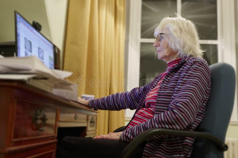 La vieja persona mayor mayor que aprende el ordenador y las habilidades en línea de Internet se guardan de Spam del timo del frau foto de archivo