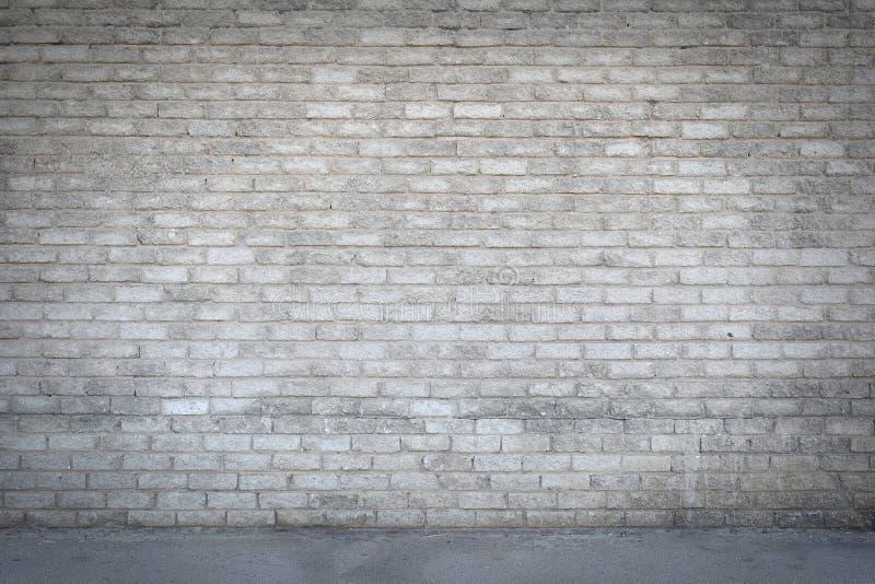 La vieja y sucia pared de ladrillo de cemento con un camino que corre delante imágenes de archivo libres de regalías