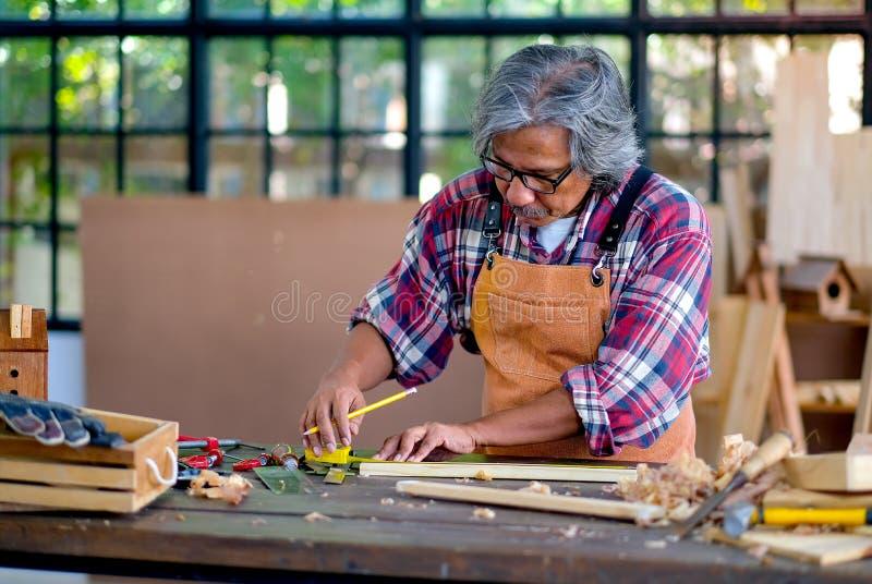 La viejos medida y trabajo del artesano con los productos de madera y también utilizan varias herramientas para ayudar del trabaj imágenes de archivo libres de regalías