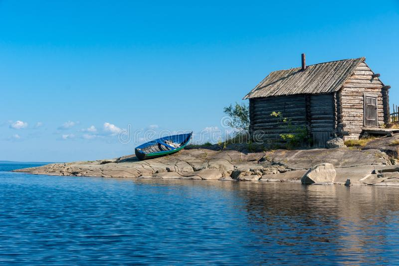 La vieux hutte et bateau en bois sur les lacs rocheux étayent, la Russie photo libre de droits