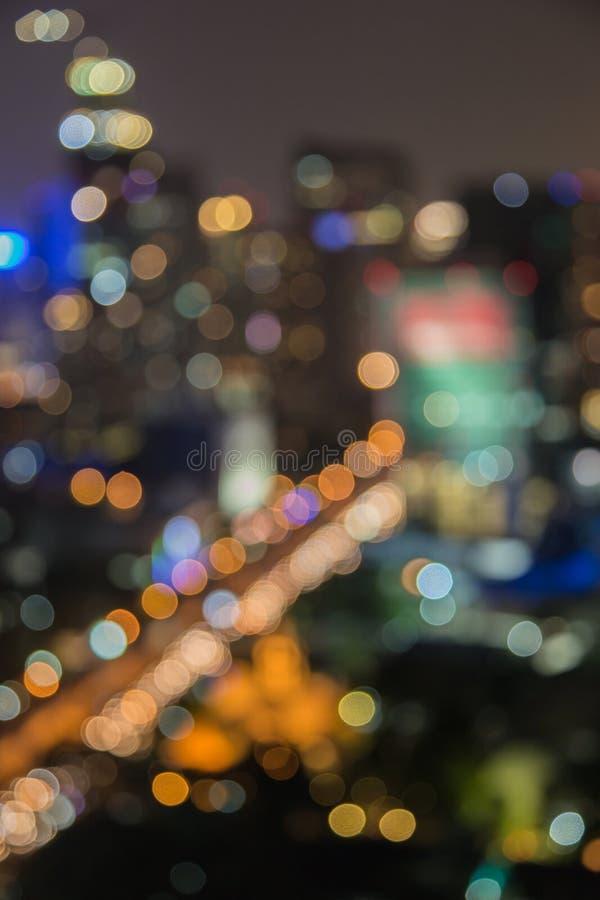 La ville s'allume le soir avec le fond de flou images stock