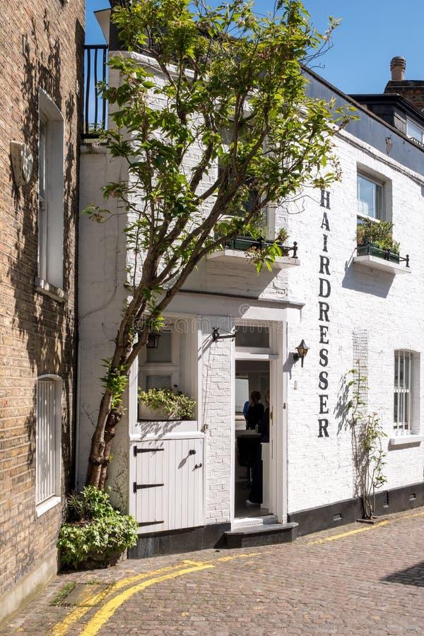 La visión abajo de un peculiar maúlla calle secundaria en Kensington, Londres Reino Unido, mostrando edificios pintados blanco imágenes de archivo libres de regalías