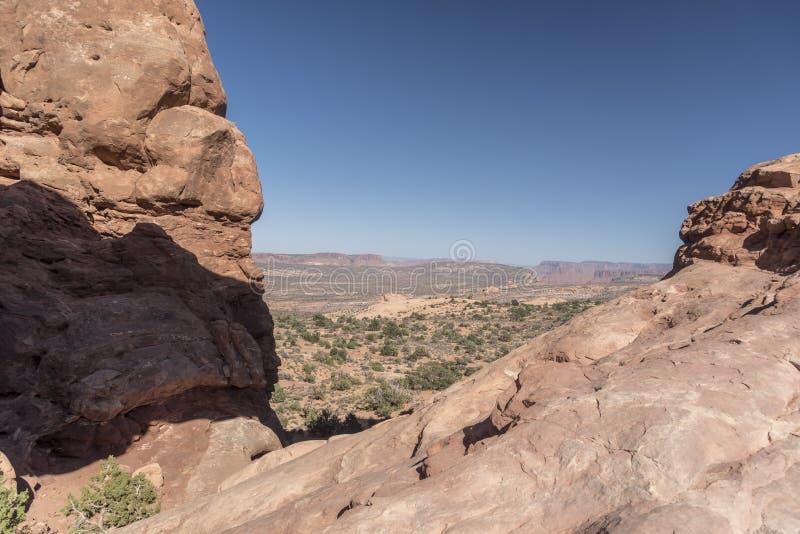 La visión desde el arco de la ventana y el cepillo del norte del desierto, arquea el parque nacional Moab Utah fotografía de archivo