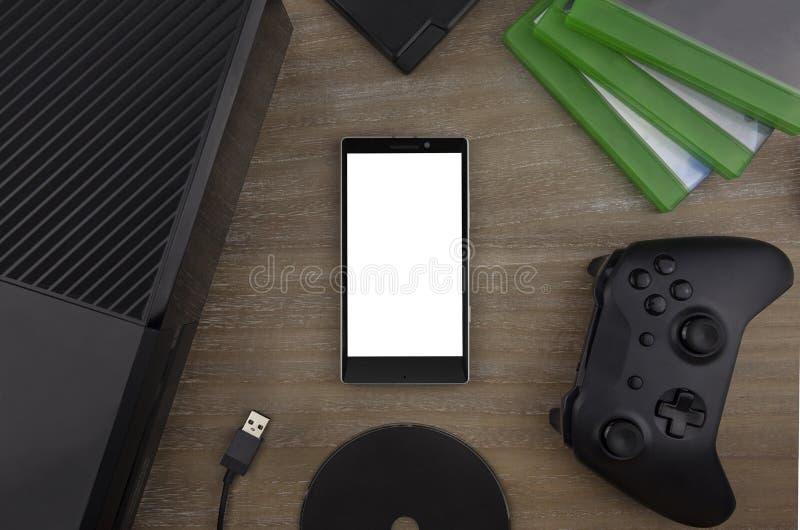 La visión desde el top en el teléfono elegante, la videoconsola, el cojín del juego, los discos del juego y el juego complementan fotos de archivo
