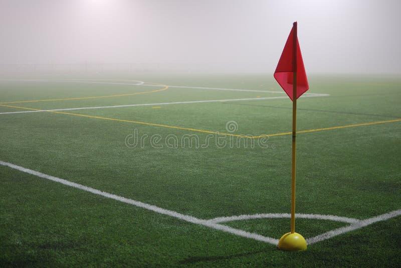 La visión desde la bandera de la esquina roja en un campo de fútbol en niebla foto de archivo