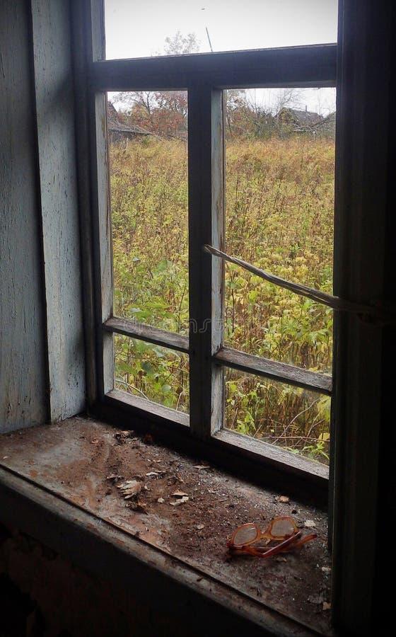 La visión desde la ventana de una casa abandonada del pueblo foto de archivo