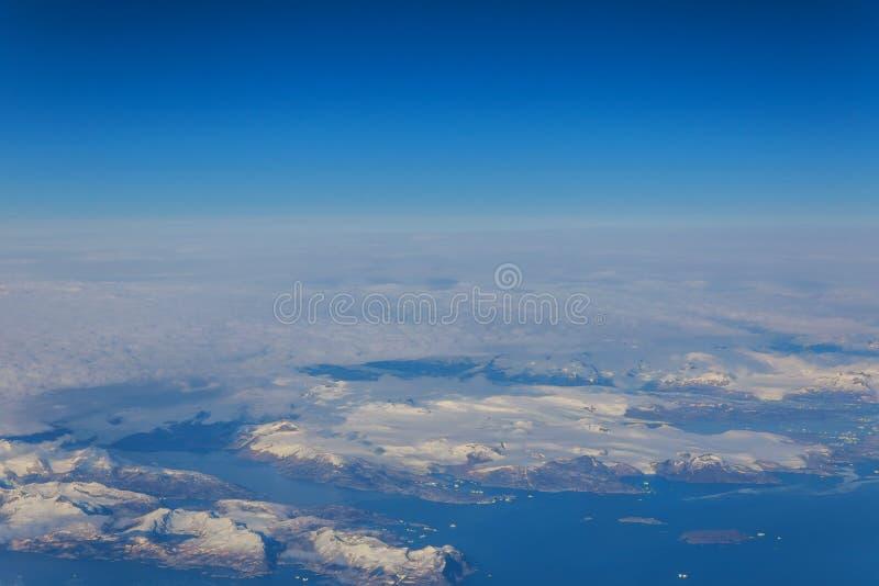 la visión desde la ventana del aeroplano los picos de montaña nevados se nubla mirar a escondidas de las nubes foto de archivo libre de regalías
