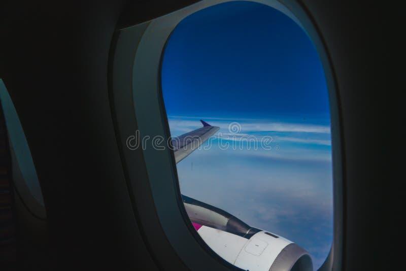 La visi?n desde la ventana plana mira hacia fuera para considerar el cielo azul hermoso fotografía de archivo