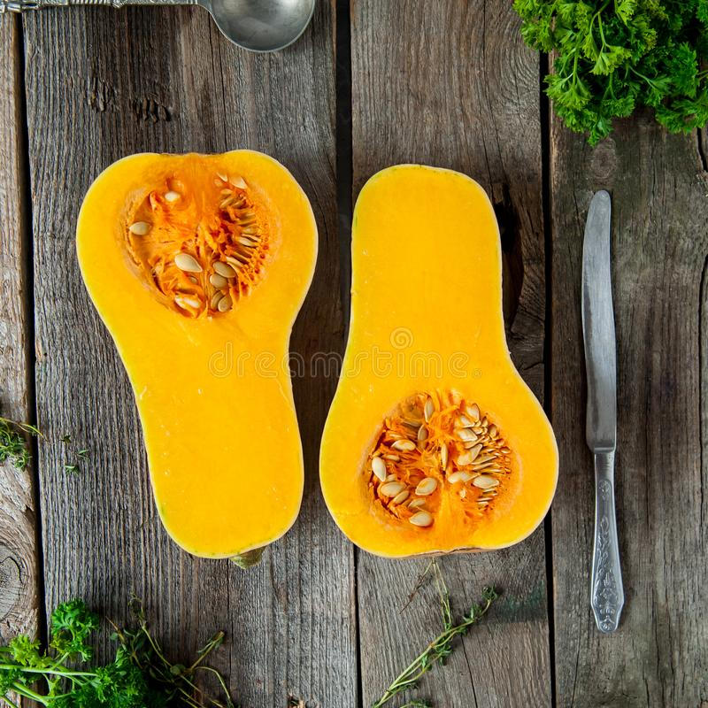 La visión superior cortó la calabaza anaranjada madura con las semillas en la tabla de madera rústica Vegetariano, vegano, comida fotos de archivo