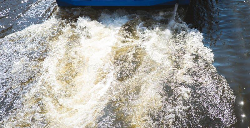 La visión superior, flotadores del barco de motor en un río marrón, el sol se refleja en la superficie Paisaje abstracto, imagen  fotografía de archivo