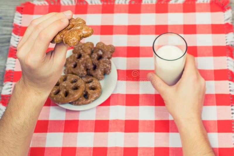 La visión superior OM sirve las manos del ` s que sostienen la galleta y el vidrio de leche sobre el ch fotografía de archivo
