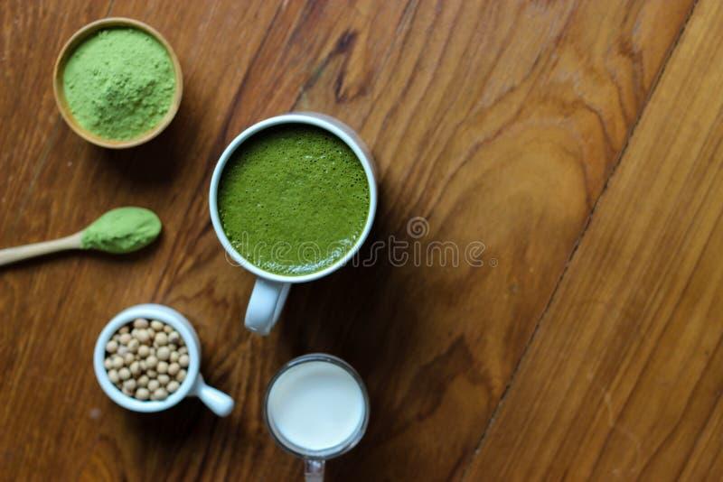 La visión superior, se cierra encima del Latte caliente de Matcha del té verde en etiqueta de madera oscura fotografía de archivo libre de regalías