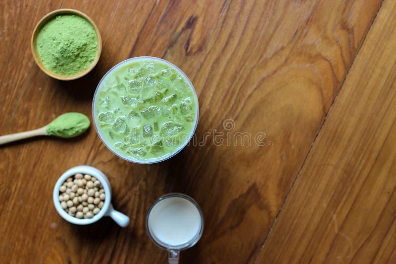 La visión superior, se cierra encima del Latte helado de Matcha del té verde en TA de madera oscura fotos de archivo libres de regalías
