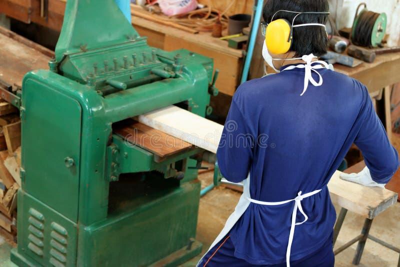 La visión superior, trabajador está trabajando con el cepillado de la máquina de madera Él está llevando el equipo de seguridad e fotos de archivo libres de regalías