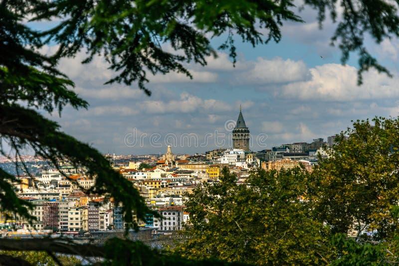 La visión a través de árboles y los arbustos al distrito Galata con el Galata se elevan en Estambul en Turquía imagen de archivo