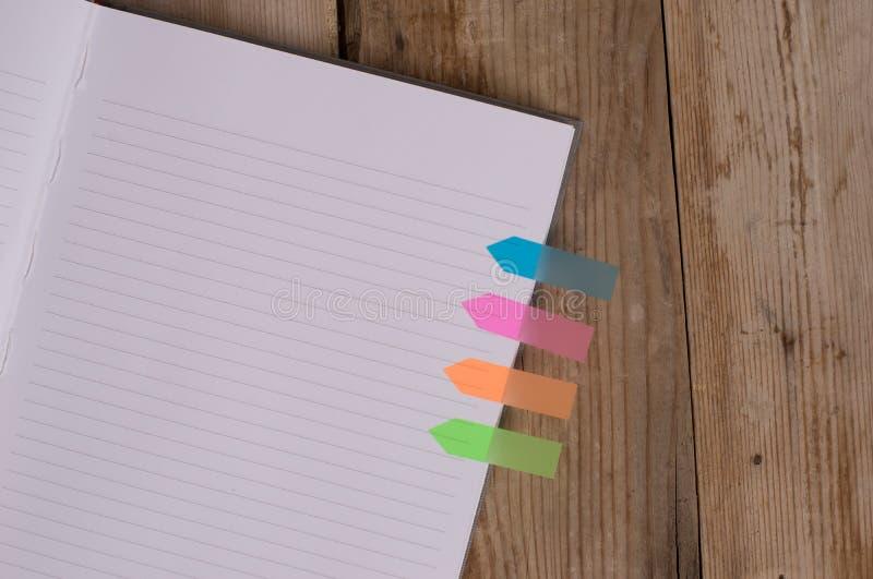 La visi?n superior rayada aline? banderas coloreadas de la flecha del cuaderno de cubierta cuatro duros insert? la madera oscura  imágenes de archivo libres de regalías