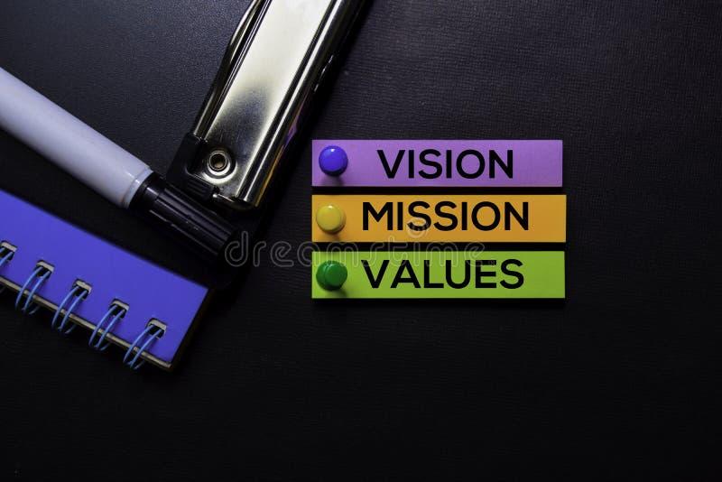 La vision, mission, évalue le texte sur les notes collantes d'isolement sur le bureau noir Concept de stratégie de mécanisme photographie stock libre de droits