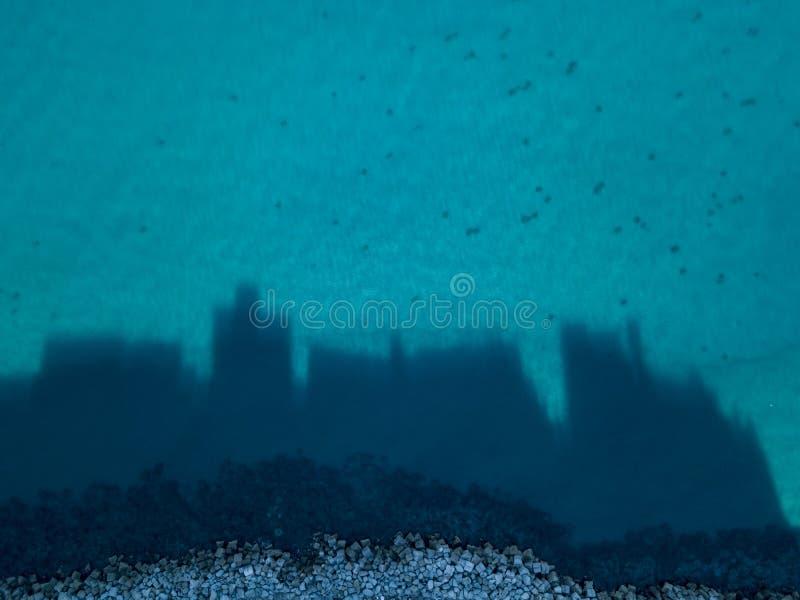 La vista aérea de Pizzo Calabro, sombras de los edificios que proyectaban sobre el mar, siluetas de casas proyectó sobre el mar imagen de archivo libre de regalías