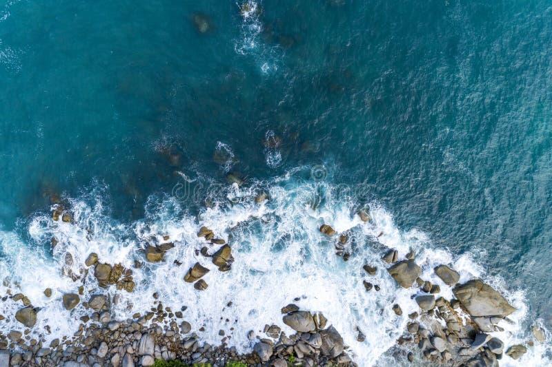 La vista aerea delle onde di schianto sulle rocce abbellisce la vista della natura ed il bello mare tropicale con la vista della  fotografia stock libera da diritti