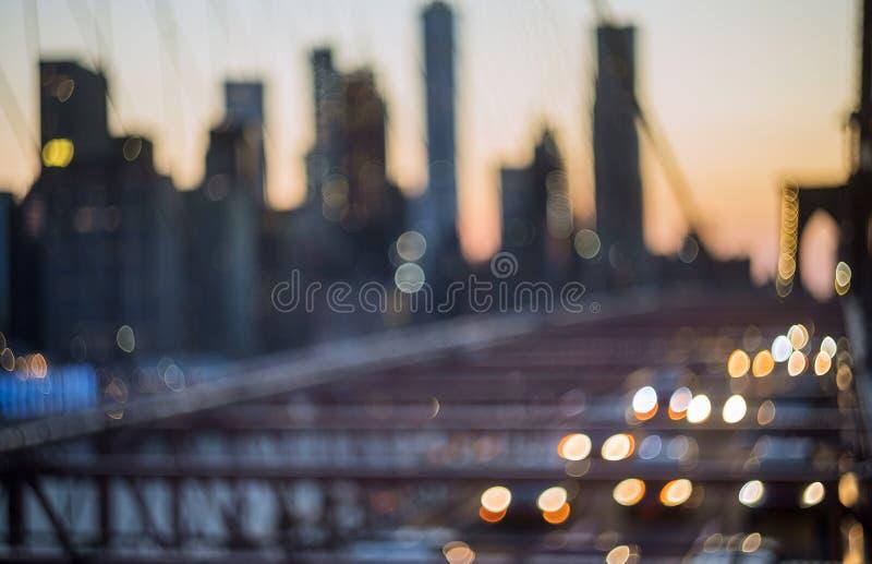 La vista aerea sopra Manhattan con il ponte di Brooklyn ha offuscato l'orizzonte di vista di notte delle luci, fondo astratto fotografia stock libera da diritti