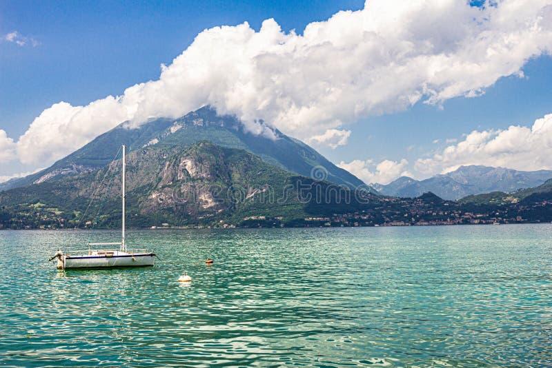 La vista al velero ancló en puerto el pueblo de Varenna en el lago Como Paisaje escénico en las montañas de las montañas del fond imagen de archivo libre de regalías
