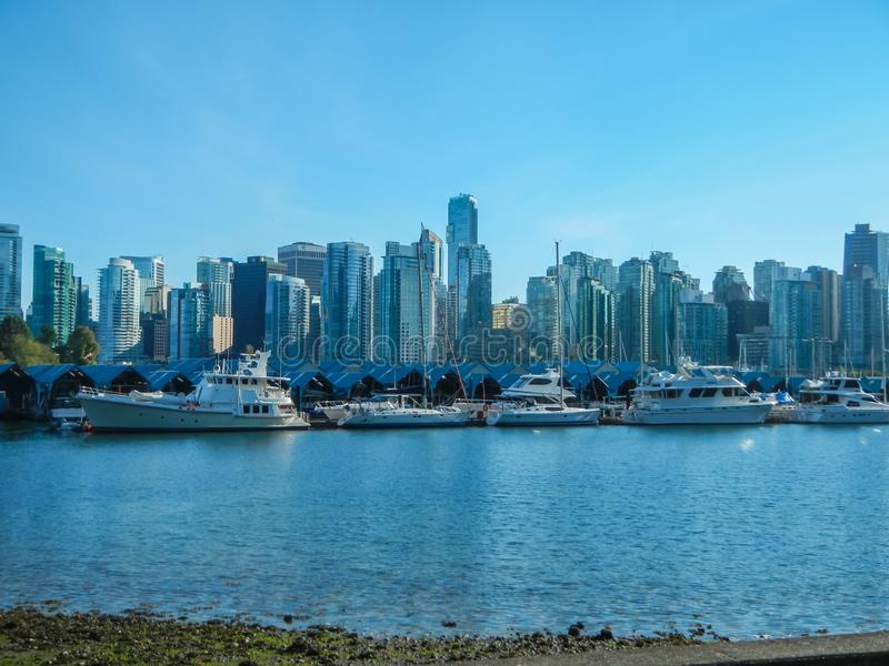 La vista all'orizzonte del centro di Vancouver dal porto del parco di Stanley può fotografia stock libera da diritti