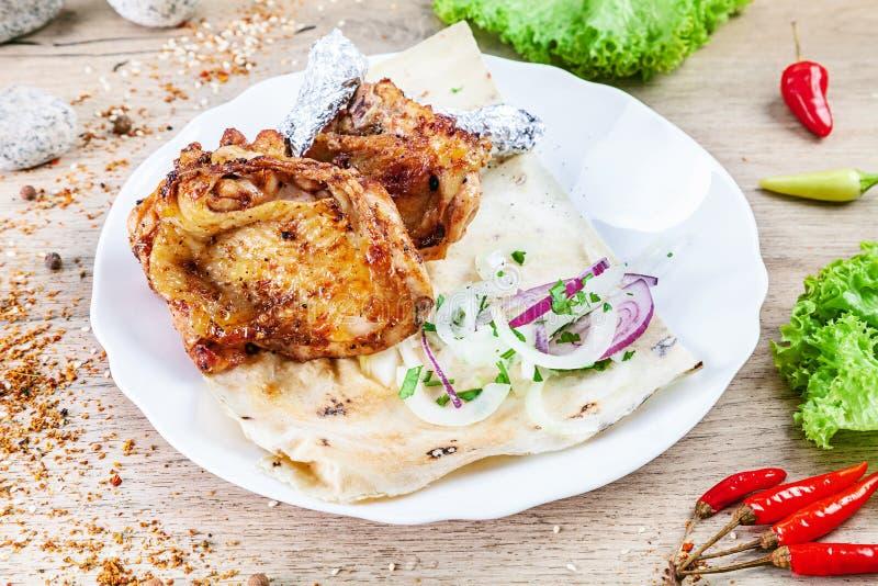 La vista alta vicina sul barbecue o lo shashlik dalla coscia di pollo è servito sul piatto sulla tavola di legno La cucina dell'E immagini stock libere da diritti