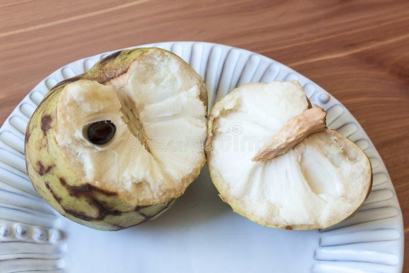 La vista cercana de una annona cherimola abierta quebrada de la fruta de la chirimoya en un blanco estrió la placa que mostraba e imagenes de archivo