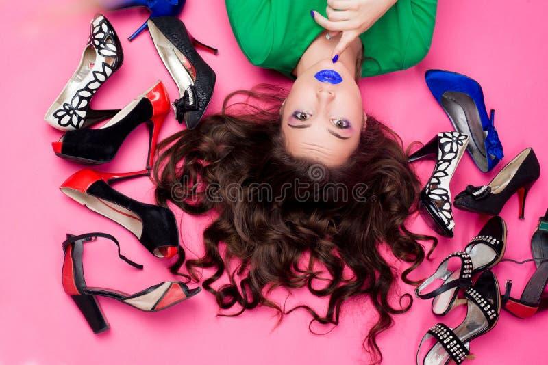 La vista da sopra della ragazza castana graziosa con capelli ondulati lunghi ed il blu compongono la menzogne sul pavimento rosa, fotografia stock libera da diritti