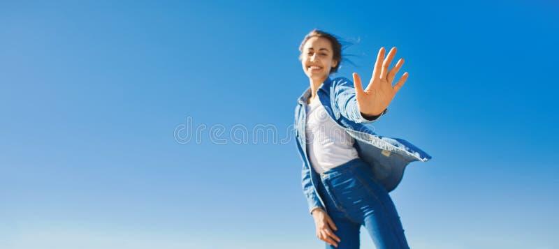 La vista dal basso di una donna attraente sorridente dei giovani in jeans copre al giorno soleggiato sui precedenti del cielo blu immagini stock