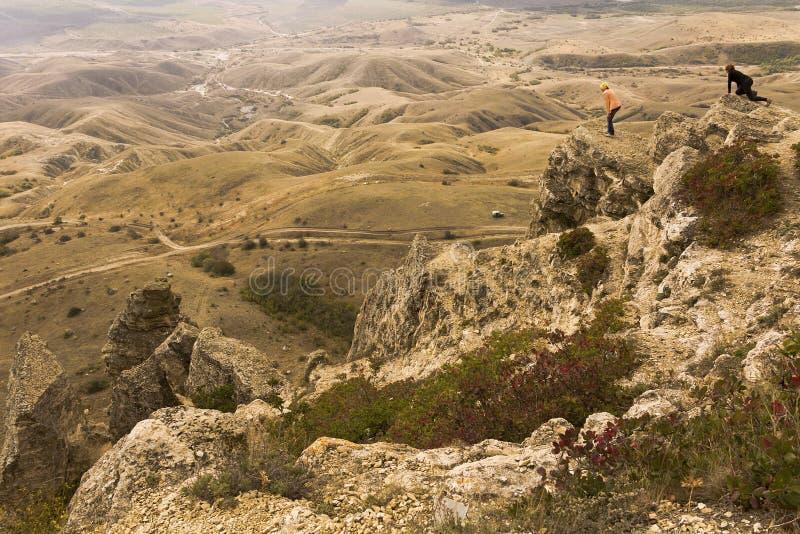 La vista dalla cima della montagna alla valle I viaggiatori guardano giù fotografia stock libera da diritti