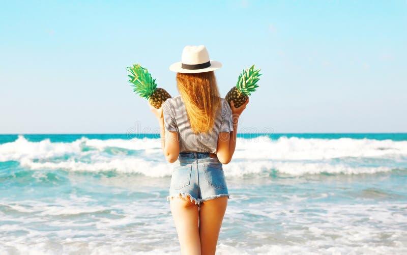 La vista dalla parte posteriore della donna con due ananas gode del mare immagine stock libera da diritti