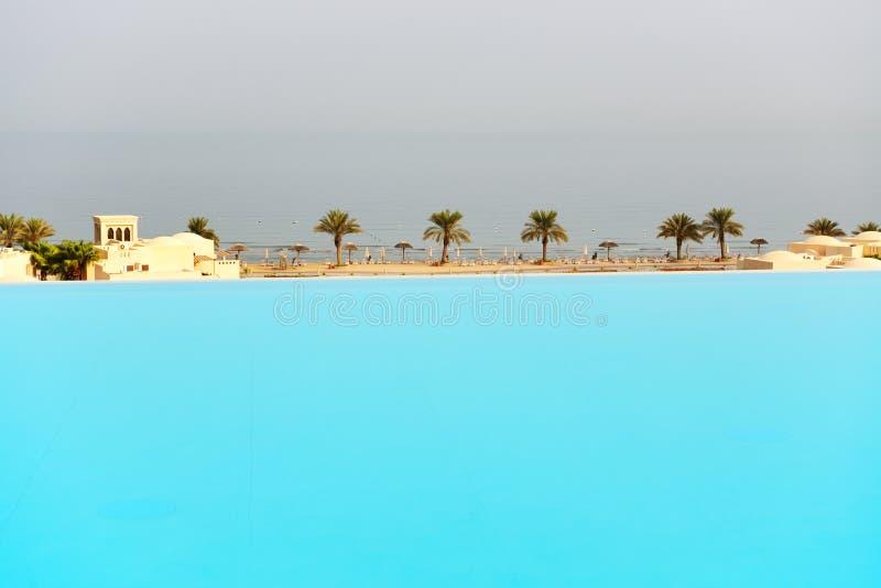 La vista dalla piscina su una spiaggia fotografie stock libere da diritti