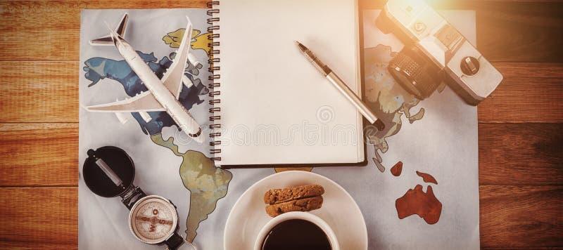 La vista de arriba de la taza de café con la cámara y el diario trazan imagen de archivo libre de regalías